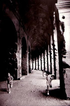 Two boys compete in a running race around the corridors of the Colosseum, Rome