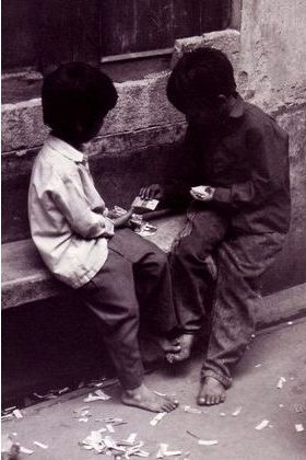 Two boys sit in a doorway in a side street in Old Delhi playing with cards made from old cigarette packets.
